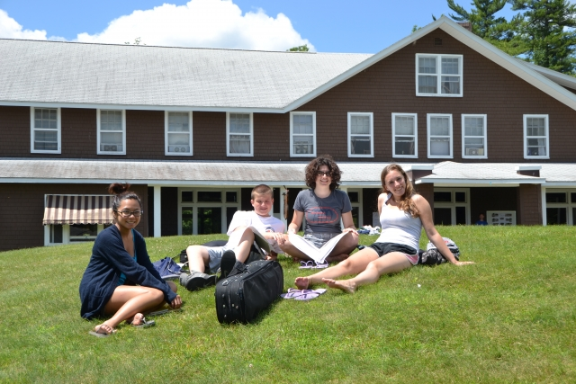 musicians sitting on a hill in front of the lodge at New England music camp